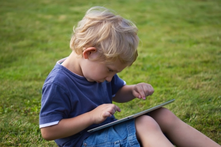 The blond boy is  sitting on lawn and playing with the PC tablet photo