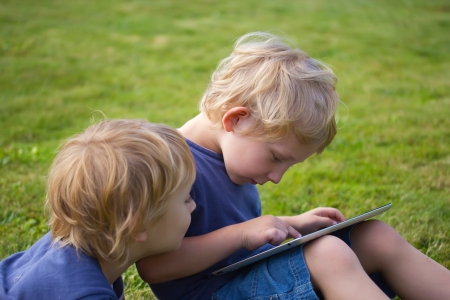 The blond boys  brothers  are playing with the PC tablet outdoor  photo