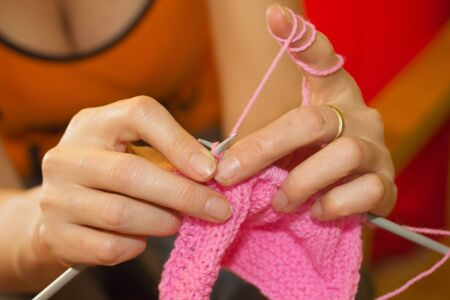 Hands of a married woman knitting with pink wool  photo
