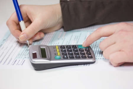 Hand filling income tax forms with calculator and pen