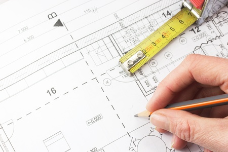Planning for house construction   Architect holding a pencil, on the table is a tape measure