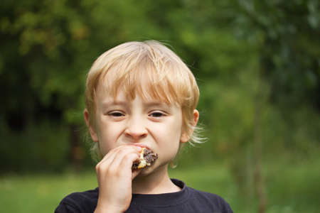 Blond  boy eating cake outdoors  green background  photo