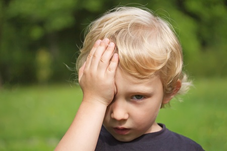 Portrait of a blond young boy covering his eyes