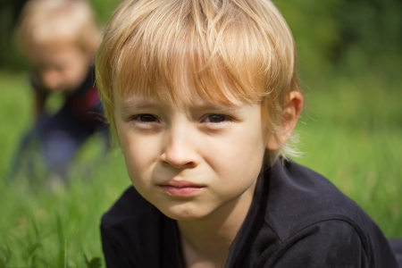 Portrait of a blond boy in the garden  His brother is in the background  photo