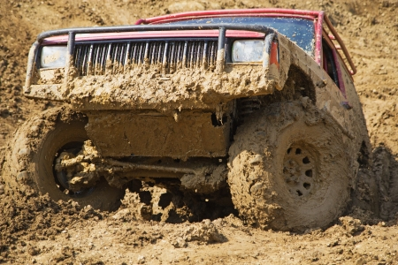 muddy tracks: SUV overcomes steep muddy slope  All potential trademarks are removed