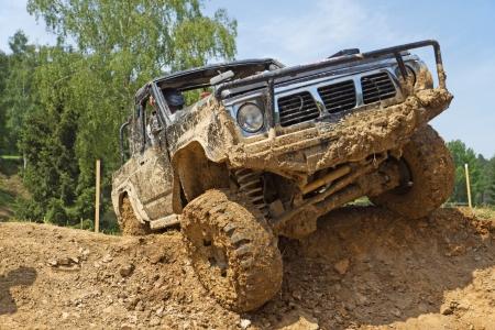 SUV는 모든 잠재적 인 상표가 제거 가파른 진흙 투성이의 경사를 극복 스톡 콘텐츠