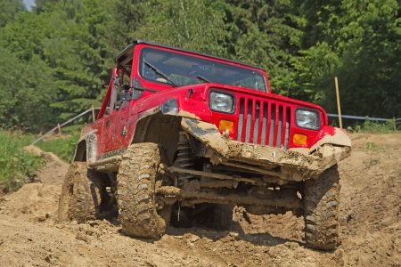 Red off-road vehicle in muddy terrain  All potential trademarks are removed