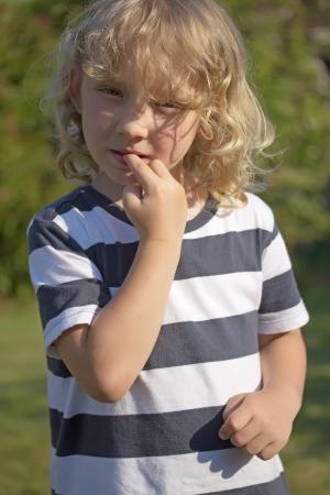 Der blonde Junge in einem gestreiften Hemd beißt seine Nägel. Vertikal. Standard-Bild - 21172754