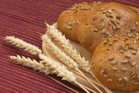 Various types of whole wheat bread and wheat ears lying on a wooden board  photo