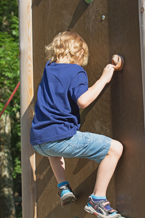 The blond boy climbs the climbing wall in summer day. photo