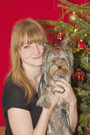 Young smiling woman with red hair is holding Yorkshire Terrier. Christmas tree in the background. photo