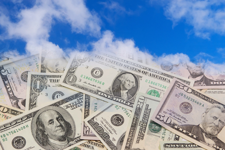 U.S. banknotes falling from the blue sky. photo