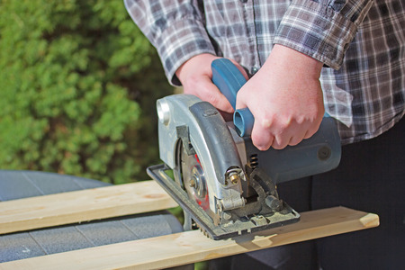 Closeup view of a man in a checkered shirt that is cutting wooden board electric circular saw