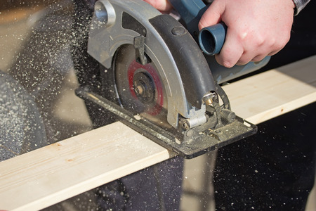 Closeup view of a man that is cutting wooden board electric circular saw