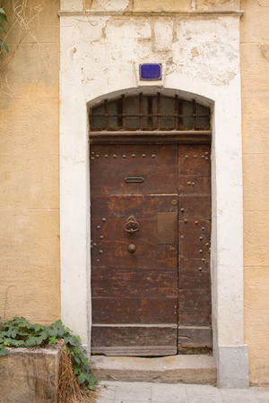 view of a wooden doorway: Old wooden entrance door to the house. Mediterranean architecture. Stock Photo