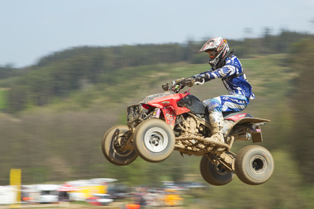 MOHELNICE,  CZECH REPUBLIC - APRIL 19: Racer in blue  is jumping a quad motorbike in the International Championship of the Czech Republic 2014 on April 19, 2014  in MOHELNICE, Czech Republic.