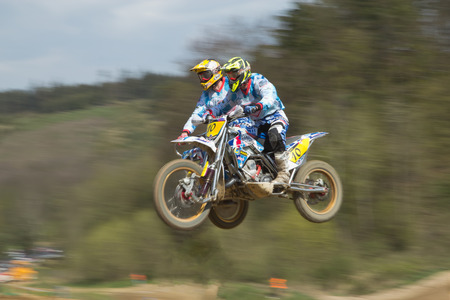 sidecar motocross racing: MOHELNICE, CZECH REPUBLIC - APRIL 19. Two racers in blue are jumping a sidecar in the International Championship of Czech Republic 2014 on April 19. 2014  in the town of Mohelnice, Czech Republic.  Editorial