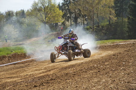 MOHELNICE,  CZECH REPUBLIC - APRIL 19: Racer is riding a quad with a smoking engine in the International Championship of the Czech Republic 2014 on April 19, 2014  in MOHELNICE, Czech Republic.