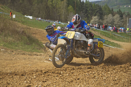 sidecar motocross racing: MOHELNICE, CZECH REPUBLIC - APRIL 19. Racers in blue are passing a sweep by sidecar in the International Championship of Czech Republic 2014 on April 19. 2014  in the town of Mohelnice, Czech Republic.  Editorial