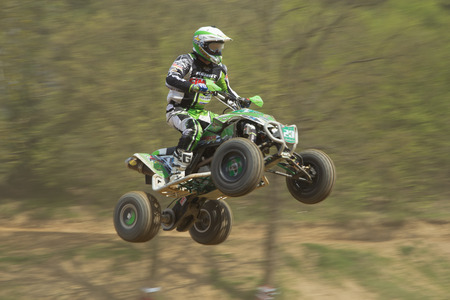 MOHELNICE,  CZECH REPUBLIC - APRIL 19: Racer in green is jumping a quad motorbike in the