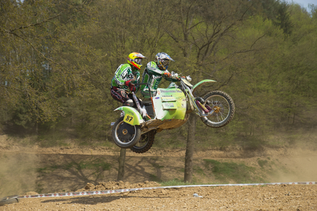 sidecar motocross racing: MOHELNICE, CZECH REPUBLIC - APRIL 19. Two racers in green are jumping a sidecar in the International Championship of Czech Republic 2014 on April 19. 2014  in the town of Mohelnice, Czech Republic.