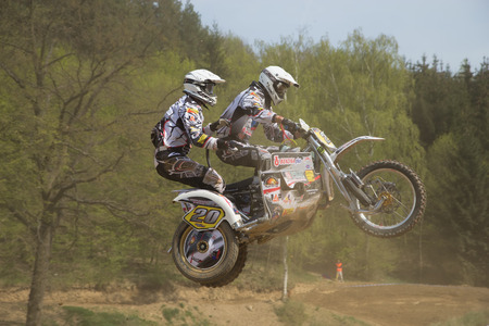 sidecar motocross racing: MOHELNICE, CZECH REPUBLIC - APRIL 19. Two racers in black and white are jumping a sidecar in the International Championship of Czech Republic 2014 on April 19. 2014  in the town of Mohelnice, Czech Republic.