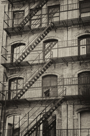 Vintage photo of old building with outdoor staircase (New York City, USA).Vertically.