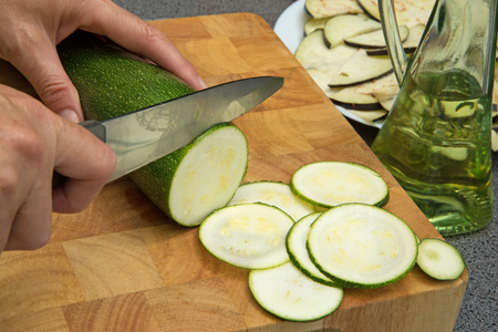 Woman's hand is slicing the zucchini on a wooden board.
