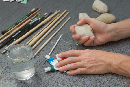 Handmade - stone painting. production decoration. Preparation for painting. Female hand are holding a blank stone.