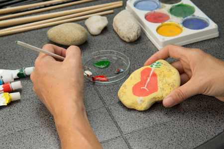 Handmade - stone painting. production decoration. Female hand are drawing red heart on the stone. Horizontally.