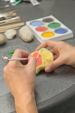 Handmade - stone painting. production decoration. Female hand are drawing red heart on the stone. Vertically. Stock Photo