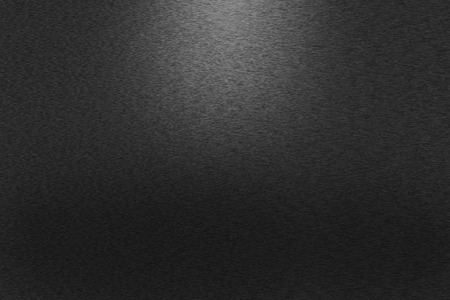 Pattern of brushed black metal background. Subdued light is in the upper middle part of the background.