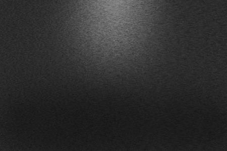 Patroon van zwart geborsteld metaal achtergrond. Gedempt licht in het bovenste middelste deel van de achtergrond. Stockfoto