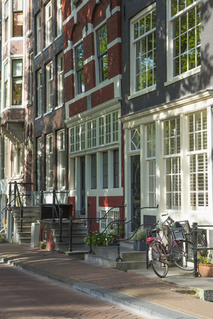 Sunny street in Amsterdam with a bicycle parked outside the house  (Amsterdam, Netherlands). photo