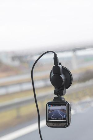 Functionele auto-camera gemonteerd op de voorruit. Foto geschoten tijdens het rijden. Highway Bridge is op de achtergrond.