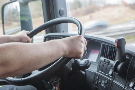 cabaña: Vista de cerca de las manos del conductor de camión que está sosteniendo el volante. Foto disparaban en la cabina del vehículo. Foto de archivo