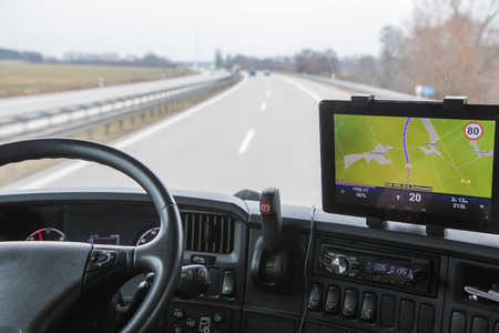 ciężarówka: Widok ruchu drogowego przez przednią szybę kabiny ciężarówki. Nawigacyjny jest zamontowany na tablicy rozdzielczej.