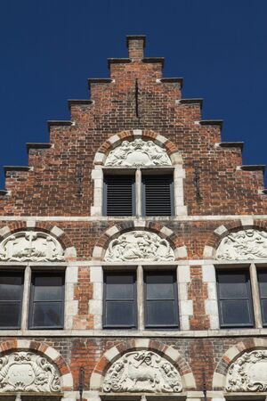 stucco house: The original stucco on the ancient brick house in Bruges (Flanders, Belgium). Front view. Blue sky in the background. Stock Photo