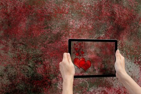 whose: In the bottom rightt of the photo are hands holding tablet, whose screen contains photo of the grunge texture background with the red hearts. Background of the photo contains the same iron grunge texture background.