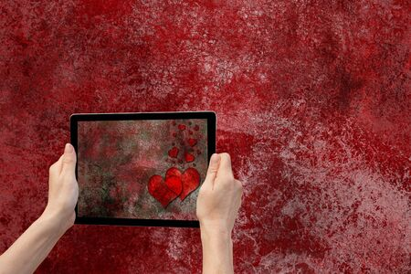 tred: In the bottom left of the photo are hands holding tablet, whose screen contains photo of the grunge red and black texture background with the red hearts. Background of the photo contains tred iron grunge texture background.