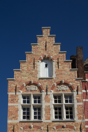 house gable: The unique example of medieval architecture. Gable roof of the brick historic house (Bruges, Belgium). Front view.