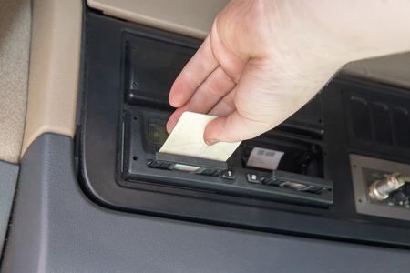 トラックのタクシー内のデバイスにタコグラフ カードを挿入するトラックの運転手の手のクローズ アップ ビュー。