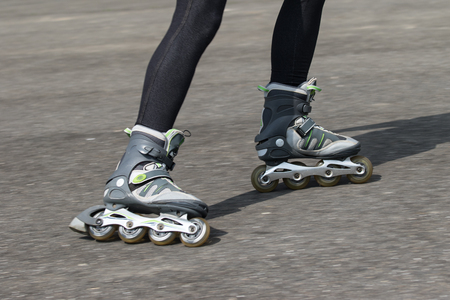 inline: Dynamic closeup view of in-line skates driving along the asphalt road. All potential trademarks are removed.