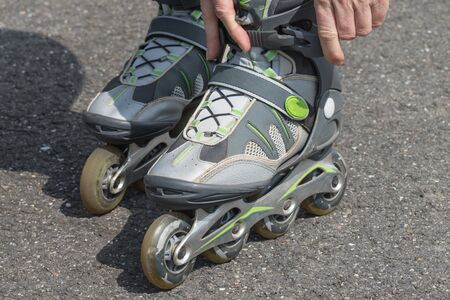 rollerblade: Closeup view of a woman putting on her rollerblades outdoors. All potential trademarks are removed. Stock Photo