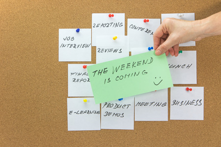 affixed: White paper notes with various written to-do tasks affixed to the corkboard.  Female hand holding a green card with the inscription The weekend is coming in the foreground.