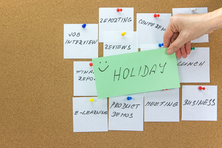 affixed: White paper notes with various written to-do tasks affixed to the corkboard.  Female hand holding a green card with the inscription Holiday in the foreground. Stock Photo