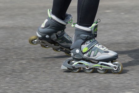 inline: Dynamic closeup view of a woman on inline skates driving along the asphalt road. All potential trademarks are removed.