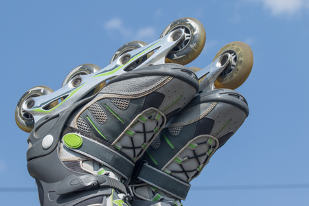 rollerblades: Closeup view of the raised feet putting on to rollerblades against a blue sky.All potential trademarks are removed. Horizontally.