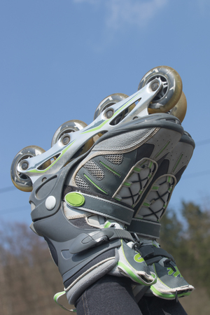 rollerblades: Closeup view of the raised feet putting on to rollerblades against a blue sky.All potential trademarks are removed. Vertically.All potential trademarks are removed. Stock Photo