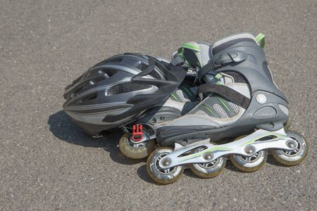 rollerblades: Helmet and rollerblades are lying on asphalt road. All potential trademarks are removed.